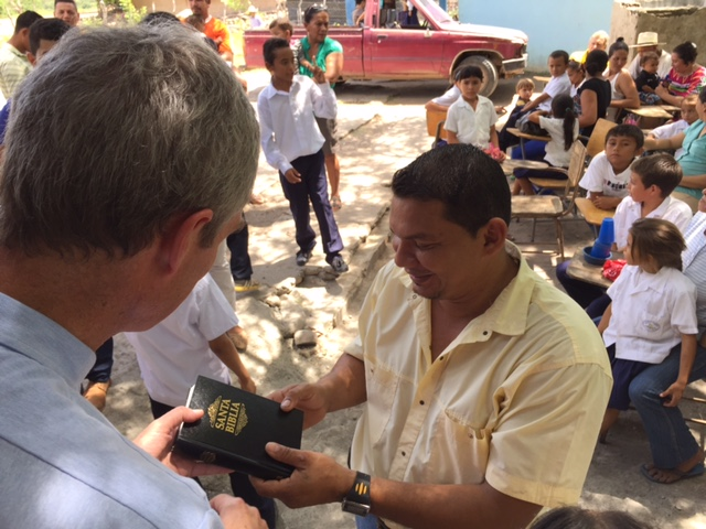 Pastor Scott presenting a Bible to the principal of the Benito Montoya E.S.