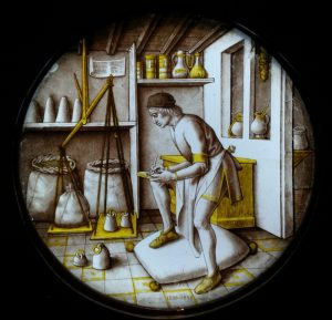 "A merchant is at work in his warehouse surrounded by the tools of his trade. Standing on a woolsack, he weighs goods on a large balance using a set of standardised avoirdupois weights. The large scales are falsely balanced with ropes of different lengths, possibly a typical commentary on the theme of working for profit.The subject of this roundel has recently become clear. It is thought to represent one of the Ages of Man."" -- [from the Victoria and Albert Museum. 1475-1500"