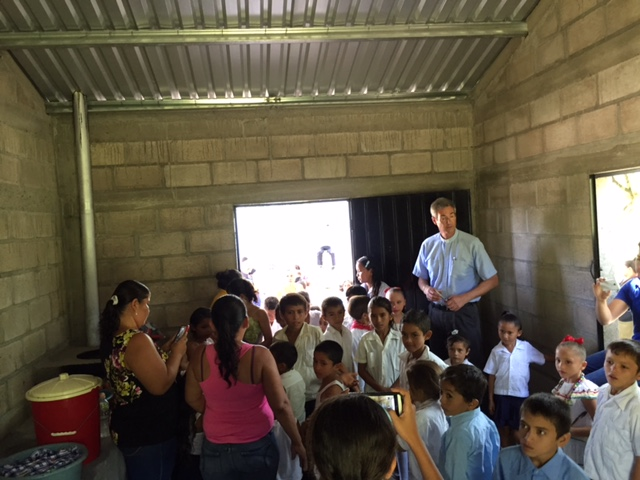 Pastor Scott and children inside the newly built kitchen building.