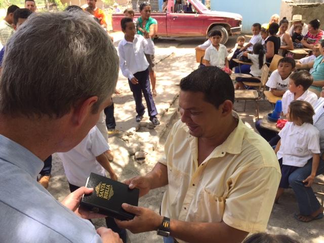 Pastor Scott presenting a Bible to the principal of the Benito Montoya E.S.