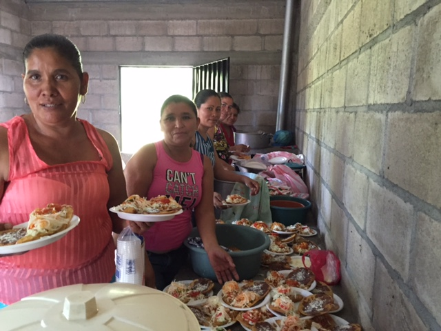 Mothers volunteer to serve up the lunch from the new kitchen.